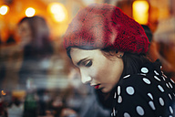 Portrait of young woman wearing red hat behind windowpane of a pub in the evening - LCUF00059