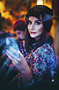 Portrait of young woman with smartphone looking through windowpane of a pub in the evening - LCUF00062