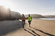 France, Crozon peninsula, young couple running on the beach - UUF08610
