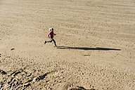 Teenage girl running on the beach - UUF08628