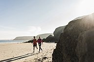 France, Crozon peninsula, young couple running on the beach - UUF08631
