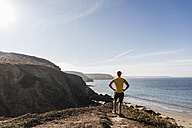 France, Crozon peninsula, sportive young man at steep coast looking at view - UUF08637