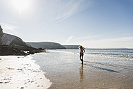 France, Crozon peninsula, teenage girl walking on the beach - UUF08643