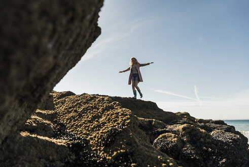 France, Crozon peninsula, teenage girl walking on rock at the coast - UUF08649
