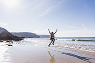 France, Crozon peninsula, teenage girl jumping for joy on the beach - UUF08655