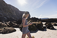 France, Crozon peninsula, teenage girl with cell phone walking on the beach - UUF08658