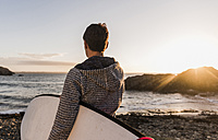 France, Bretagne, Crozon peninsula, woman on the beach at sunset with surfboard - UUF08685