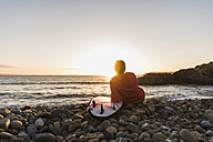 France, Bretagne, Crozon peninsula, woman sitting on stony beach at sunset with surfboard - UUF08688