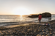 France, Bretagne, Crozon peninsula, woman standing on stony beach at sunset with surfboard - UUF08691