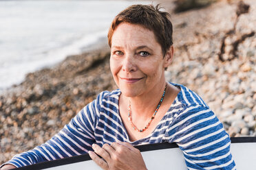 Portrait of smiling mature woman holding surfboard - UUF08694