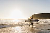 France, Bretagne, Crozon peninsula, woman walking on beach at sunset carrying surfboard - UUF08709