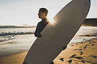 France, Bretagne, Crozon peninsula, woman standing on beach at sunset holding surfboard - UUF08712