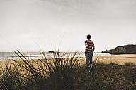 France, Bretagne, Crozon peninsula, woman standing at the coast - UUF08727