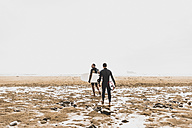 France, Bretagne, Crozon peninsula, couple walking on beach carrying surfboards - UUF08730