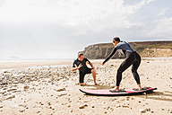 France, Bretagne, Crozon peninsula, man teaching woman surfing on beach - UUF08733