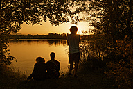 Germany, Lake Riegsee, Group of teenagers watching sunset - LBF01498
