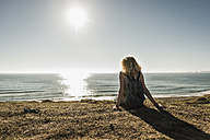 Back view of teenage girl sitting on the beach at evening twilight looking to the sea - UUF08740
