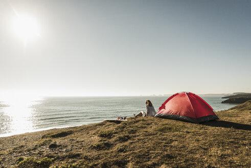 Teenage girl with surfboard camping at seaside - UUF08746
