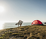 Young couple with surfboard camping at seaside - UUF08752