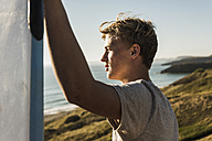 Teenage boy with surfboard looking to the sea - UUF08755