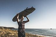 Teenage boy carrying surfboard on head - UUF08758