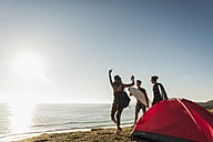 Three friends with surfboards camping at seaside - UUF08764