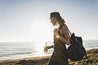 Blond teenage girl with backpack and beverage at seaside in the evening twilight - UUF08773