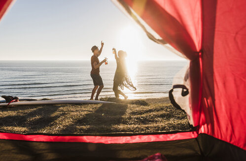 Dancing young couple camping at seaside - UUF08788