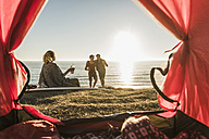 Three friends camping at seaside - UUF08791