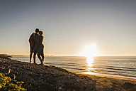 Back view of young couple in love watching sunset at seaside - UUF08797