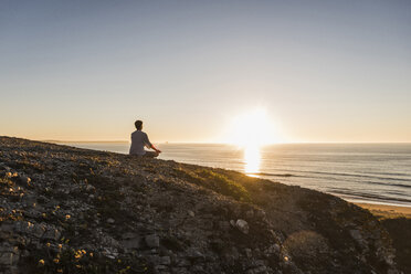 Back view of woman meditating on cliff at sunset - UUF08800