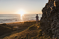 Back view of woman standing on cliff watching sunset - UUF08806