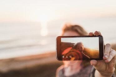 Selfie of smiling teenage girl on display of smartphone - UUF08809