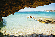 Greece, Koufonissi, Naked man jumping into clear water of the Aegean Sea - GEMF01155