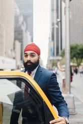 Indian businessman in Manhattan entering a yellow cab - GIOF01532