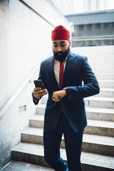 Indian businessman walking down stairs, looking at watch , holding smartphone - GIOF01544