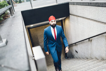 Indian businessman walking up stairs - GIOF01547