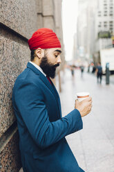 Indian businessman in Manhattan leaning against wall, drinking coffee - GIOF01559