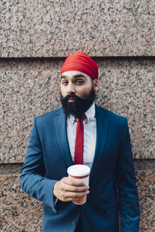 Indian businessman in Manhattan leaning against wall, drinking coffee - GIOF01562