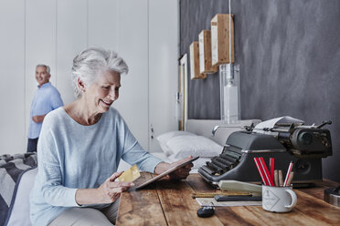 Smiling senior woman shopping online in bedroom with husband in background - RORF00310