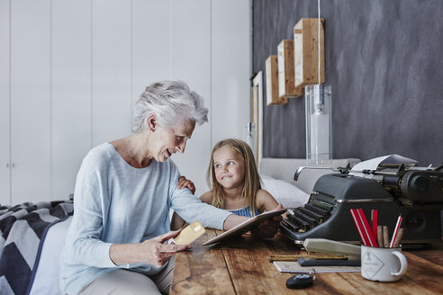 Grandmother and granddaughter shopping online at home - RORF00313