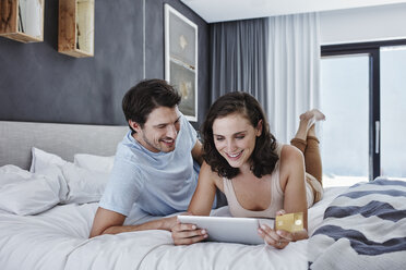 Smiling couple lying on bed shopping online - RORF00328