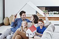 Happy family of four with house model in living room - RORF00337