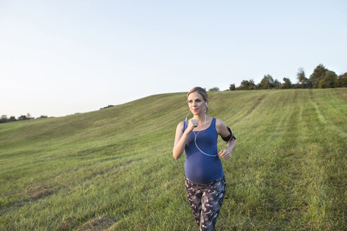 Pregnant woman jogging in field - HAPF01008