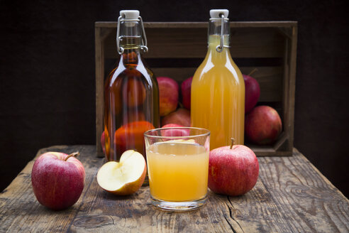 Bottle and glass of apple juice, cloudy and clear, red apples on wood - LVF05445
