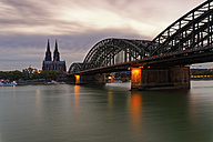 Germany, Cologne, view to Cologne Cathedral with Hohenzollern Bridge in the foreground at evening twilight - GFF00813