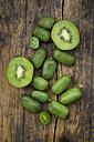 Sliced and whole hardy kiwis and sliced kiwi on dark wood - LVF05453