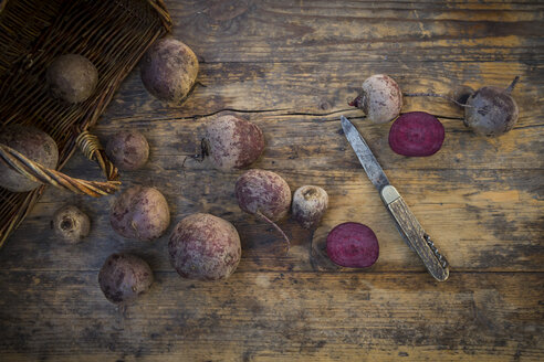 Whole and sliced beetroots and a pocket knife on dark wood - LVF05472