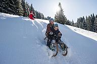 Children tobogganing in the snow - HHF05439