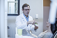 Dentist with dental mold talking to patient - ZEF10606